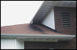 Dumping onto another roof causes shingle erosion. Instead, connect upper downspout to lower gutter.